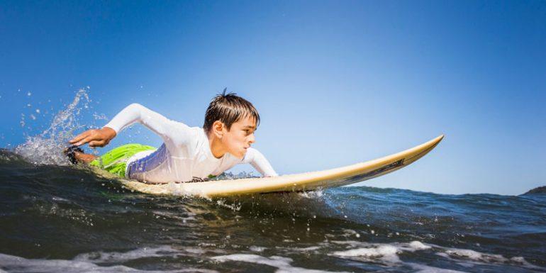 niño surfea tiburón